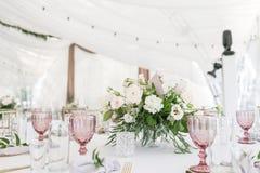 与陶器和花的美好的桌设置党、结婚宴会或者其他欢乐事件的 玻璃器皿和 免版税库存照片