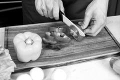 与陶瓷刀子的手切片红辣椒 免版税库存照片
