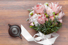 与陶瓷茶罐的惊人的花花束在木头 图库摄影