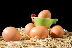 与雀斑的五个新鲜的未加工的鸡蛋在黑背景的干草 免版税库存照片