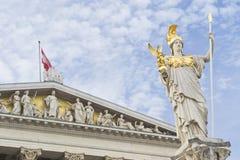 与雅典娜雕象的奥地利在作为背景使用的多云天空的parlament和旗子 库存照片