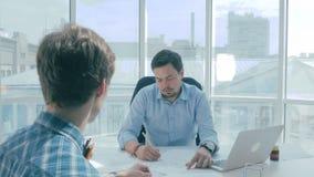 主任与雇员谈论工程项目在新的现代办公室 股票录像