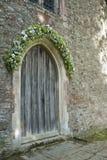 与雏菊花束的老木教会门 免版税图库摄影
