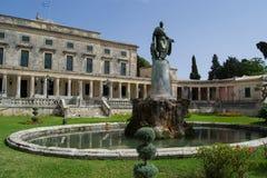 与雕塑的大厦和一个喷泉在科孚岛,希腊庭院里  免版税库存照片
