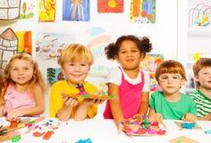 与雕塑黏土的愉快的孩子在教室 免版税库存图片