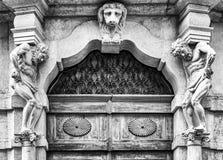 与雕象和木门户的老白色石入口 免版税库存照片