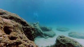 与雕象的水下的场面在海和几个潜水者的底部 股票录像