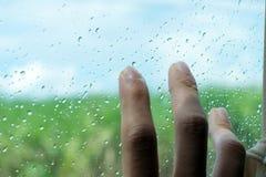 与雨下落和室外背景的手指接触玻璃表面 免版税库存图片