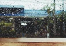 与雨珠的木表在窗口在雨天,背景的 免版税图库摄影