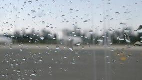 与雨珠的飞机窗口 飞机的模糊的看法通过与雨下落的平面窗口 股票视频