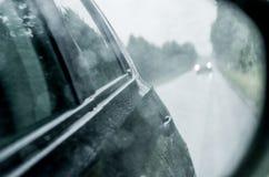 与雨的Blured背景在玻璃和汽车下降在路 库存图片