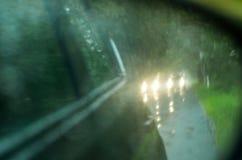 与雨的Blured背景在玻璃和汽车下降在路 库存照片