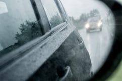 与雨的Blured背景在玻璃和汽车下降在路 免版税库存图片