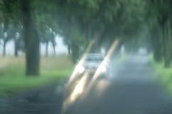 与雨的Blured背景在玻璃和汽车下降在路 图库摄影