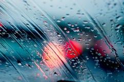 与雨的Blured背景在玻璃和汽车下降在路 免版税库存照片