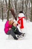 与雪人妈妈和儿子的冬天乐趣 免版税库存照片