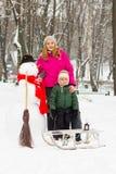 与雪人的冬天乐趣在帽子和红色围巾妈妈和儿子 免版税图库摄影