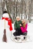与雪人的冬天乐趣在帽子和红色围巾妈妈和儿子 免版税库存照片