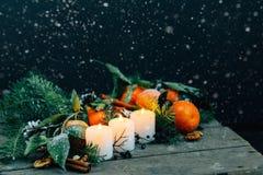 与雪剥落圣诞节构成蜜桔,杉木锥体、核桃和蜡烛在木背景,假日得体的被定调子的图象 库存图片