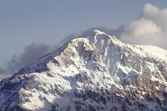 与雪和云彩的山峰 库存照片