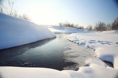 与雪和冰水的小河 库存照片
