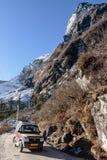 与雪和叶子的山较少树 在与土路和四轮驱动的旅游汽车下在途中对零点 库存图片