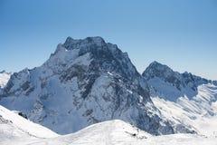 与雪和天空蔚蓝的冬天山在好太阳天 滑雪场和体育概念 高加索山脉,区域Dombay ?? 免版税库存图片