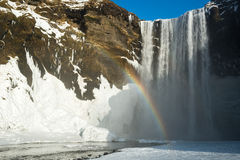 与雪和彩虹在冬天,冰岛的Skogafoss瀑布 免版税库存照片