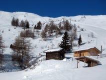 与雪和木房子的山风景 图库摄影