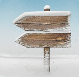 与雪和降雪bg的木方向标 two_arrows-one_ 库存图片