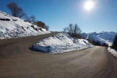 与雪在边,蓝天的空的山路曲线 库存照片