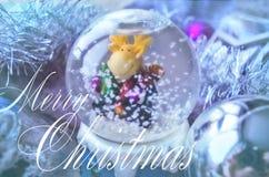 与雪地球和圣诞节树闪亮金属片的圣诞快乐和新年快乐欢乐卡片 与麋玩具的雪玻璃球 库存图片