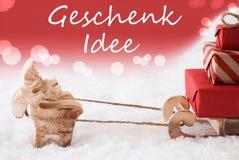 与雪撬,红色背景, Geschenk Idee的驯鹿意味礼物想法 库存图片