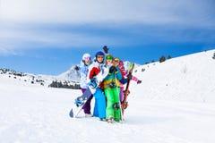 与雪板和滑雪一起的五个朋友 免版税库存照片
