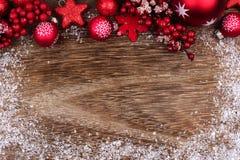 与雪框架的红色圣诞节装饰品上面边界在木头 图库摄影