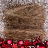 与雪框架的红色圣诞节装饰品底部边界在木头 免版税库存图片