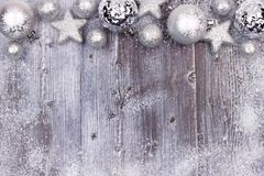 与雪框架的银色圣诞节装饰品上面边界在木头 免版税库存图片