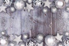 与雪框架的银色圣诞节装饰品双边界在木头 免版税库存照片
