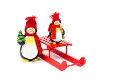 与雪橇和圣诞树的两只企鹅 图库摄影