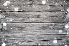 与雪的圣诞节在木头的背景和光 免版税库存照片