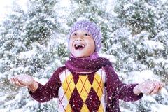 与雪的愉快的男孩作用在山 免版税库存图片