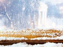 与雪的空的桌coverd在梦想和不可思议的冬天风景背景前面 对产品显示蒙太奇 免版税库存照片