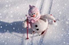 与雪的纺织品雪人滑下来小山滑雪 免版税库存图片