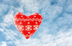 与雪的纺织品红色心脏剥落与在backg的cloudscape 库存照片