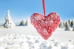 与雪的纺织品红色心脏剥落垂悬在的冬天 图库摄影