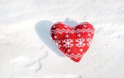 与雪的纺织品红色心脏在雪剥落 库存照片