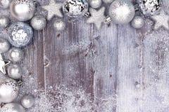 与雪的银色圣诞节装饰品上面角落边界在木头 库存照片