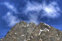 与雪的陡峭的岩石反对蓝色 免版税库存图片