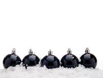 与雪的黑色圣诞节球 库存图片