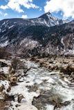 与雪的黑山在上面 在地面上是有石头、冰、黄色草和西藏人祷告旗子的冻河 免版税库存图片